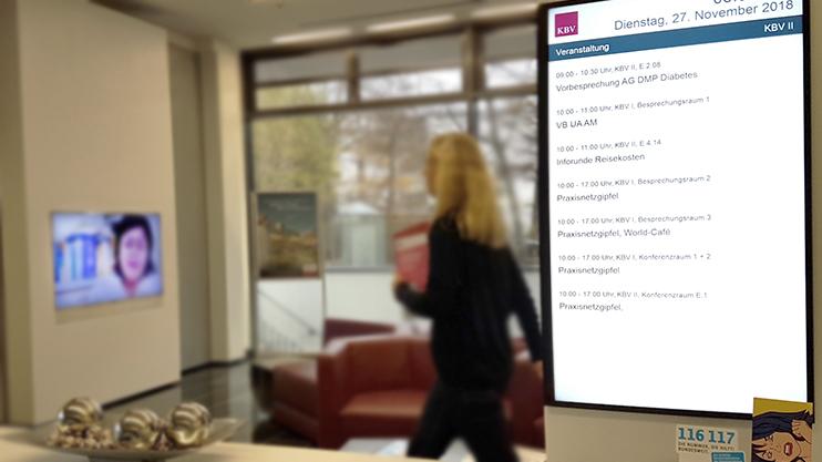 Bildschirm mit Terminen in der KBV und vorbei gehende Frau im Hintergrund