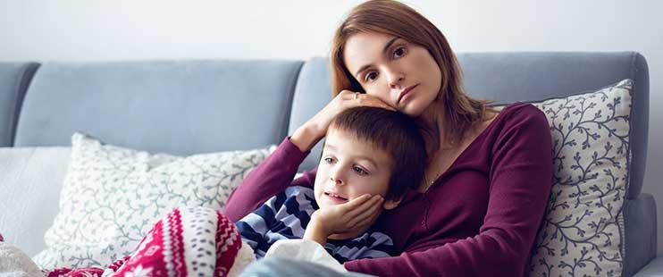 Mutter sitzt auf dem Sofa und hät den Kopf ihres Kindes