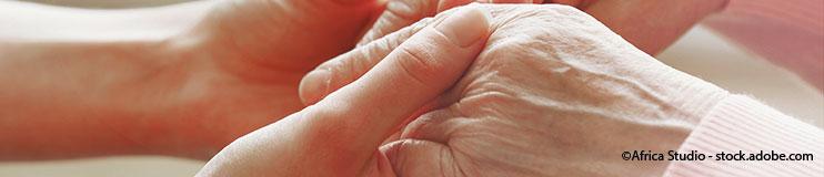 Hände einer jungen Person halten Hände einer älteren Person.