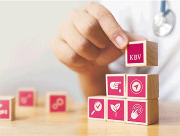 Hand einer medizinisch tätigen Person stapelt Würfel mit KBV-Logo und anderen Symbolen