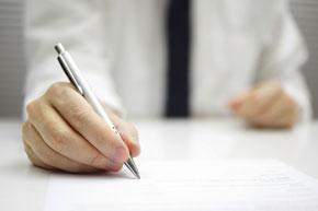 Mann schreibt mit Stift auf ein Blatt Papier