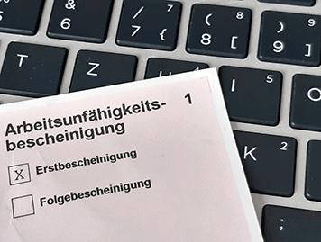 Formular Arbeitsunfähigkeitsbescheinigung auf einer Computertastatur