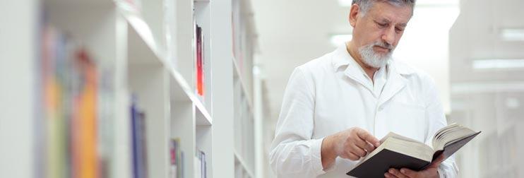 Arzt in der Bibliothek recherchiert in einem Buch